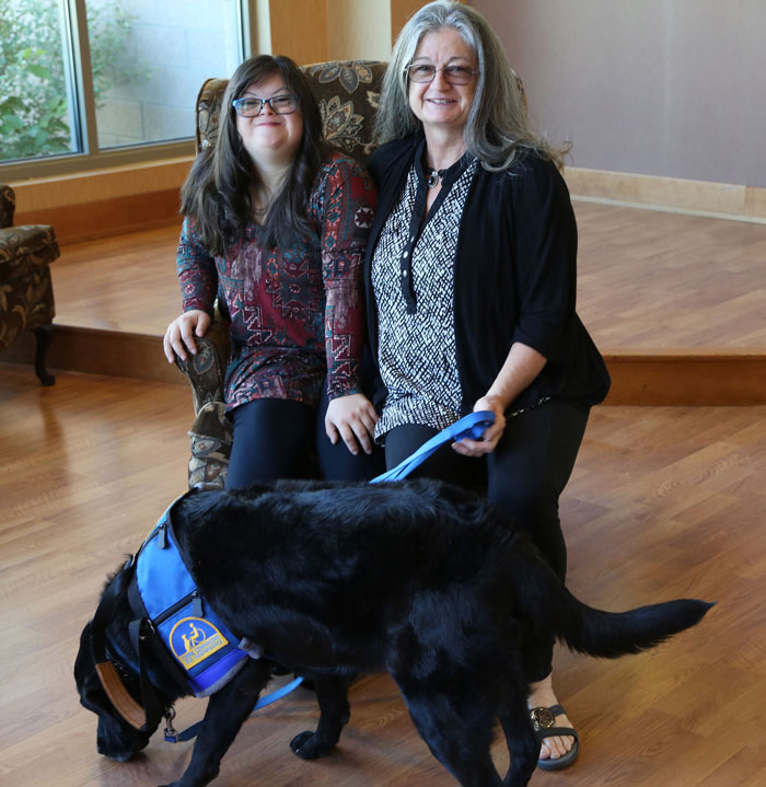 Young woman with long brown hair and glasses, with service dog and caregiver