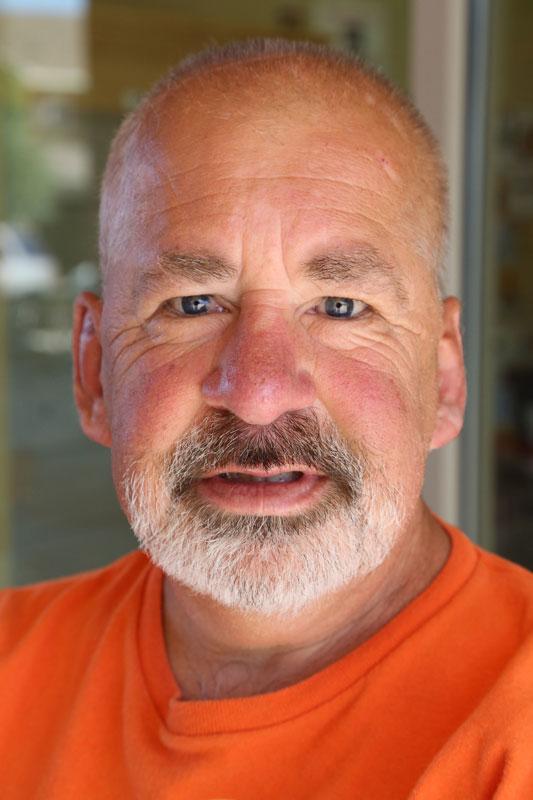 Older man with short white beard, in orange shirt