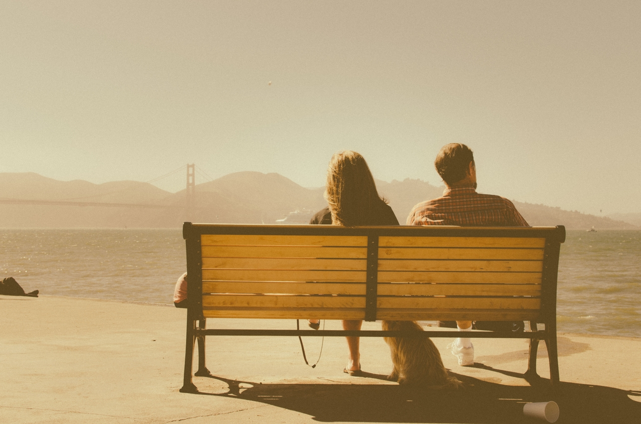 2 people sitting on a bench, facing the Golden Gate Bridge